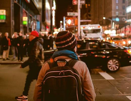 Imagem de um jovem andando pela cidade a noite