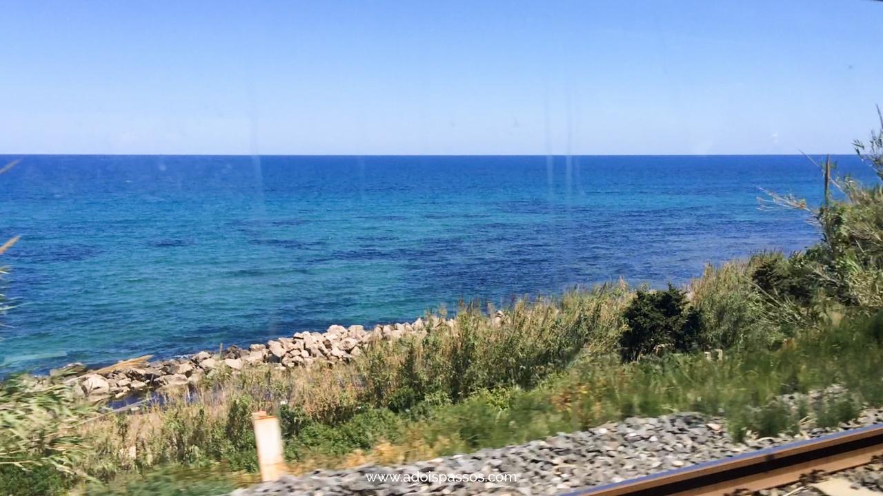 Mar visto da janela do trem em viagem pela Sicília.