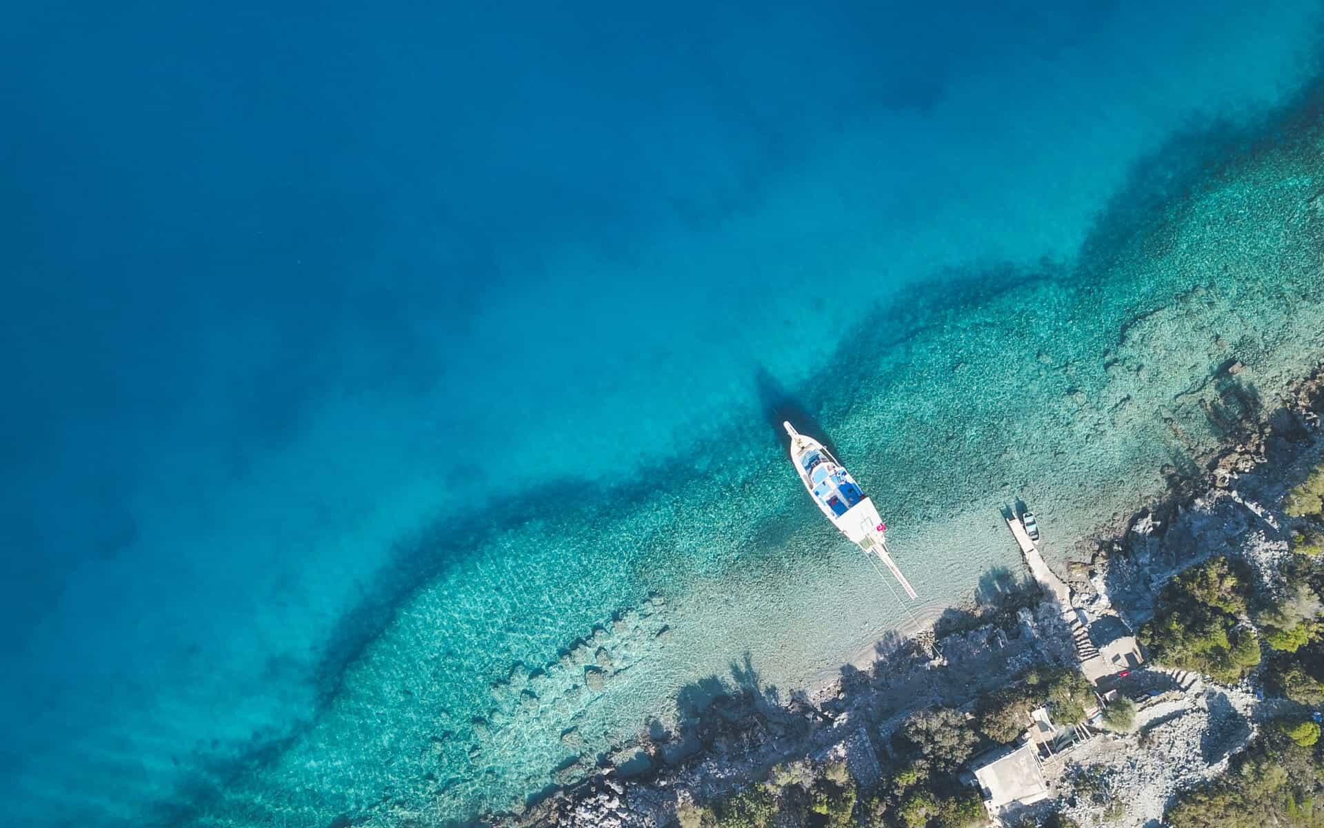 Vista aérea do mar de Oludeniz com um barco ancorado no pequeno pier.